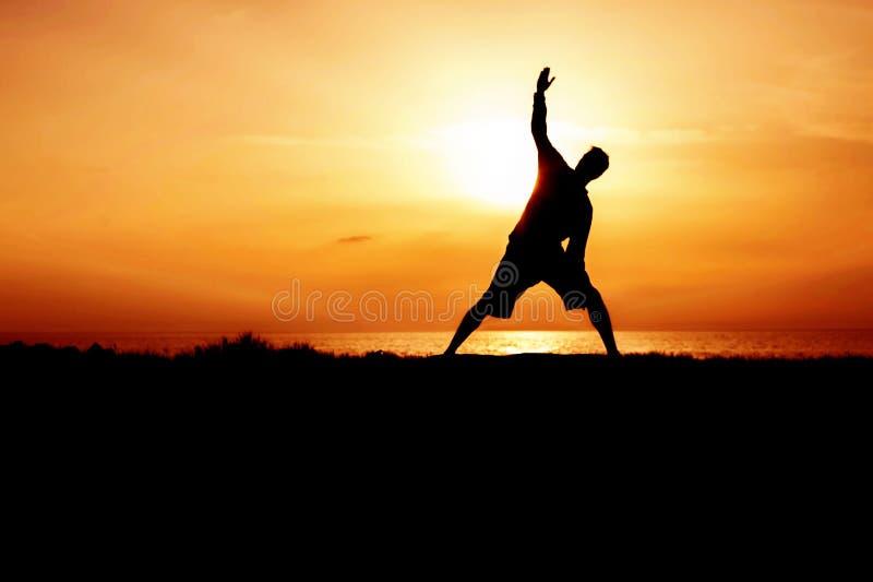 Σκιαγραφία της γιόγκας άσκησης νεαρών άνδρων Το ηλιοβασίλεμα Seacoast Trikonasana, τρίγωνο θέτει στοκ φωτογραφίες με δικαίωμα ελεύθερης χρήσης