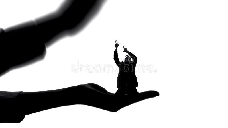 Σκιαγραφία της γυναίκας που κρατά το μικροσκοπικό άνδρα, θηλυκή αρχή, χειρισμός κυριαρχίας στοκ φωτογραφία με δικαίωμα ελεύθερης χρήσης