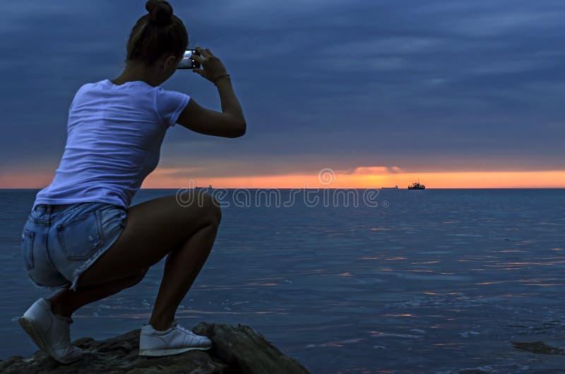 Σκιαγραφία της γυναίκας που παίρνει τη φωτογραφία μετά από το ηλιοβασίλεμα στοκ εικόνα