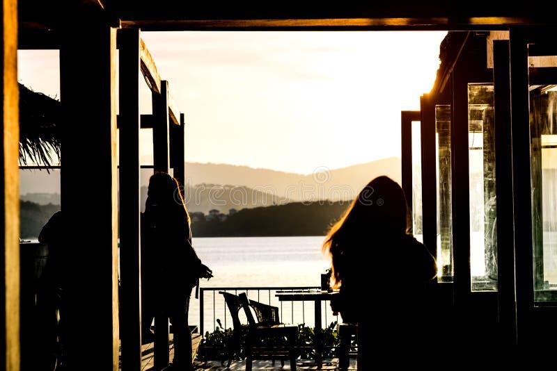 Σκιαγραφία της γυναίκας που περπατά στην πλευρά καφέδων τη θάλασσα με το beautifu στοκ φωτογραφίες με δικαίωμα ελεύθερης χρήσης
