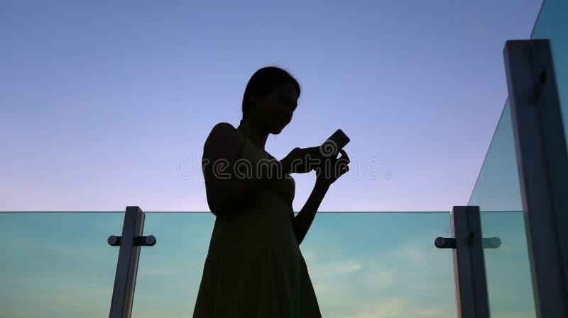 Σκιαγραφία της γυναίκας που χρησιμοποιεί το smartphone στο ηλιοβασίλεμα στη στέγη του κτηρίου στοκ εικόνες με δικαίωμα ελεύθερης χρήσης