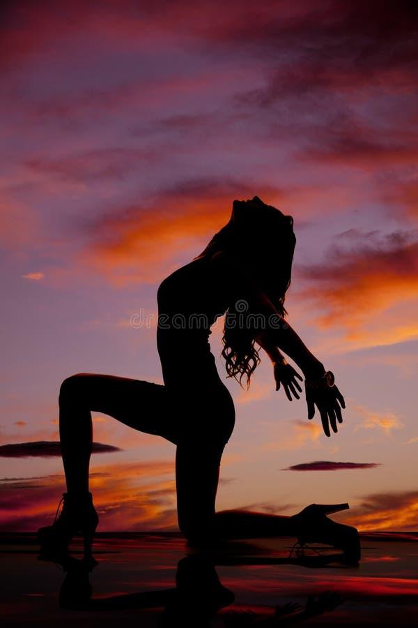 Σκιαγραφία της γυναίκας σε ένα γόνατο και τα δύο χέρια πίσω από την επικεφαλής πλάτη στοκ φωτογραφία