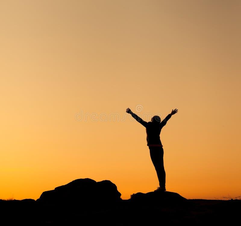 Σκιαγραφία της ευτυχούς νέας γυναίκας ενάντια στον όμορφο ζωηρόχρωμο ουρανό στοκ εικόνα