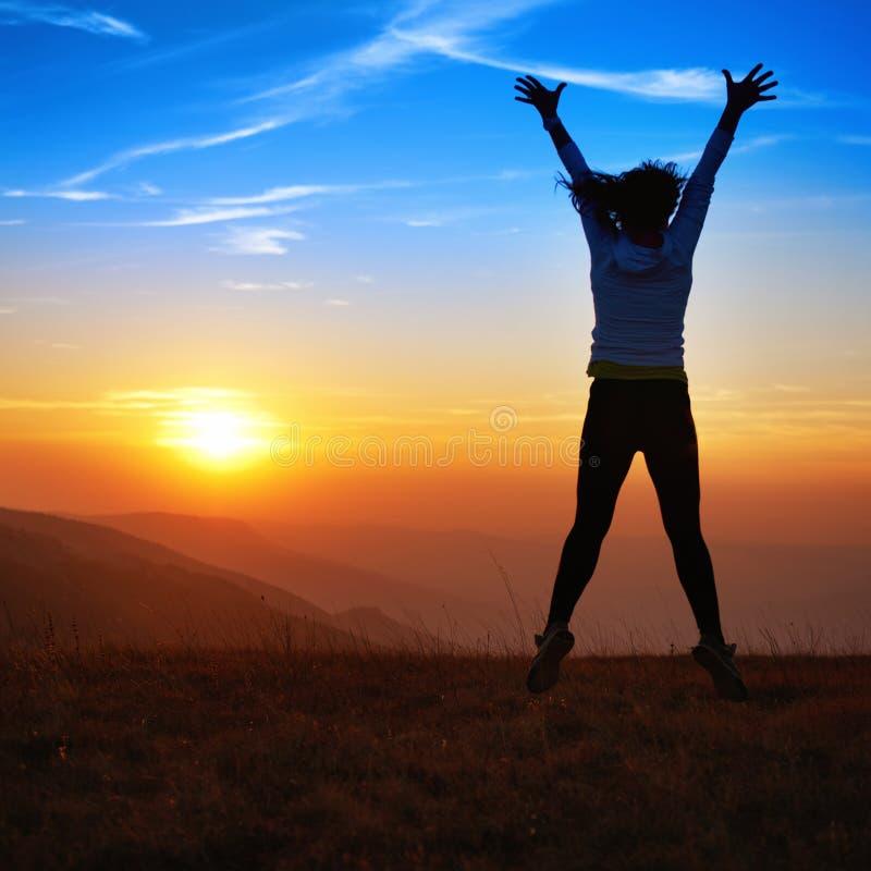 Σκιαγραφία της ευτυχούς πηδώντας νέας γυναίκας στοκ εικόνα με δικαίωμα ελεύθερης χρήσης