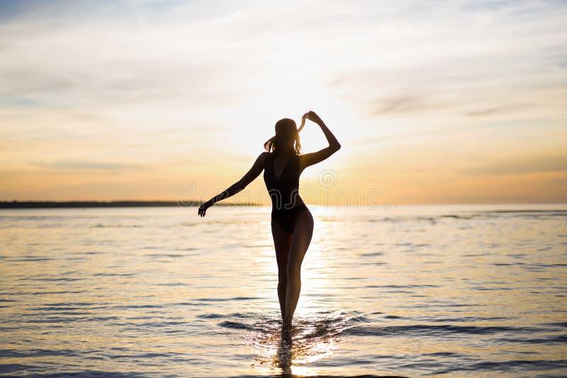 Σκιαγραφία της λεπτής προκλητικής γυναίκας στο μπικίνι που περπατά στην παραλία στοκ εικόνες