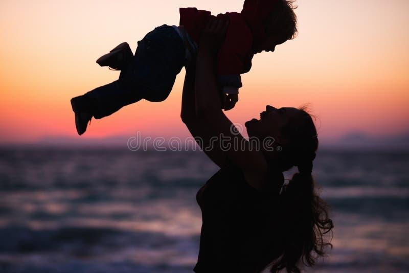 Σκιαγραφία της μητέρας που ρίχνει το μωρό επάνω στο ηλιοβασίλεμα στοκ φωτογραφίες