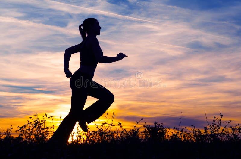 Σκιαγραφία της νέας γυναίκας που τρέχει στη φύση στοκ εικόνες με δικαίωμα ελεύθερης χρήσης
