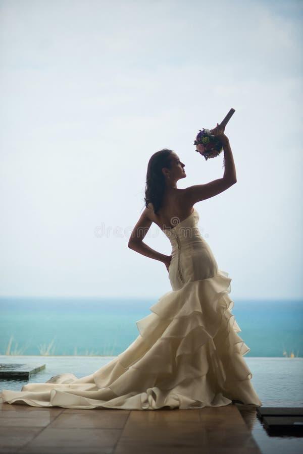 Σκιαγραφία της νύφης ενάντια στη θάλασσα η νύφη εξετάζει την ανθοδέσμη της στοκ φωτογραφίες με δικαίωμα ελεύθερης χρήσης