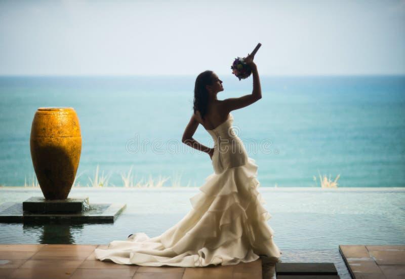 Σκιαγραφία της νύφης ενάντια στη θάλασσα Η νύφη μυρίζει την ανθοδέσμη της στοκ εικόνες