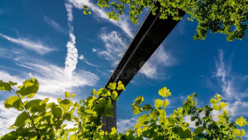 Σκιαγραφία της οδικής γέφυρας ενάντια στο μπλε ουρανό στοκ εικόνα