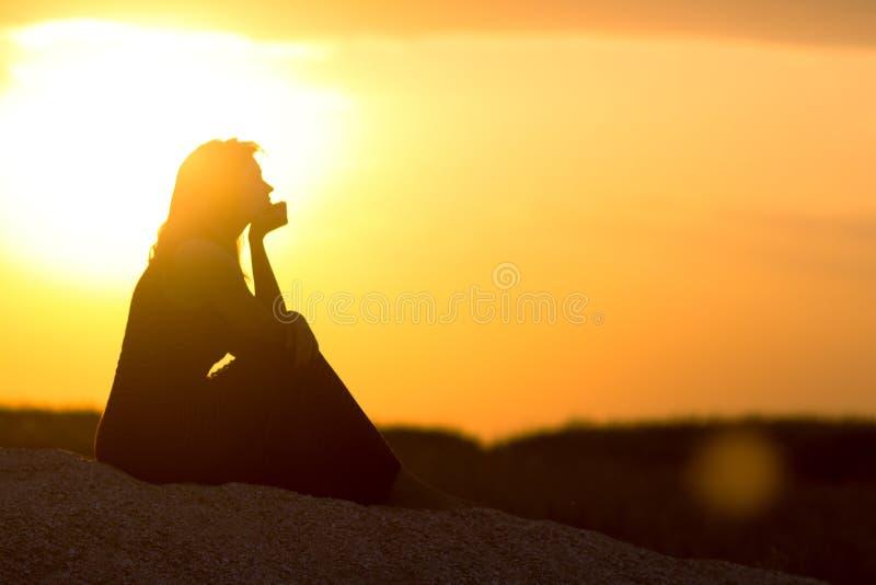 Σκιαγραφία της όμορφης στοχαστικής συνεδρίασης κοριτσιών στην άμμο και της απόλαυσης του ηλιοβασιλέματος, ο αριθμός της νέας γυνα στοκ εικόνες με δικαίωμα ελεύθερης χρήσης