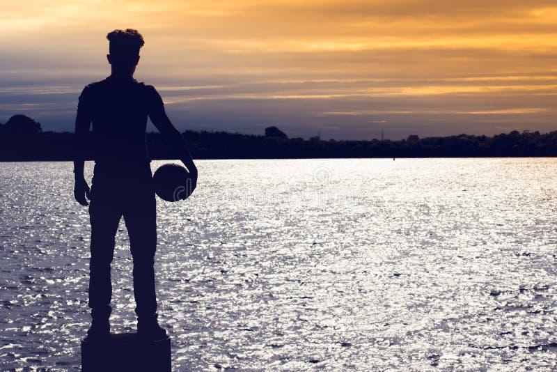 Σκιαγραφία του αγοριού ποδοσφαιριστών ποδοσφαίρου που στέκεται και που κρατά μια σφαίρα στην παραλία στοκ εικόνες