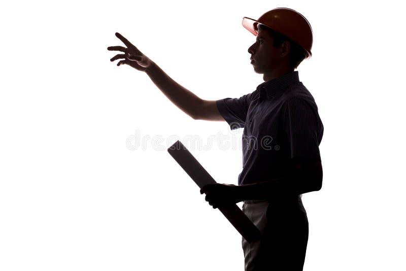 Σκιαγραφία του αρσενικού μηχανικού οικοδόμησης με το πρόγραμμα κτηρίου ι στοκ φωτογραφία