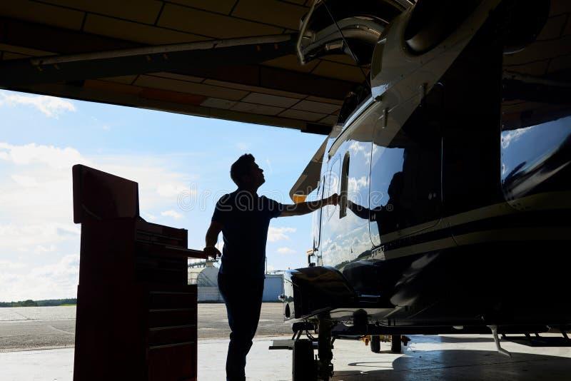 Σκιαγραφία του αρσενικού μηχανικού Aero που εργάζεται στο ελικόπτερο στο υπόστεγο στοκ φωτογραφίες