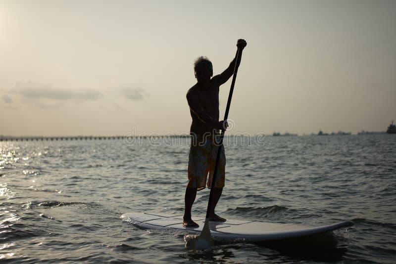 Σκιαγραφία του ασιατικού συνταξιούχου στον υπαίθριο αθλητισμό κυματωγών στοκ φωτογραφίες με δικαίωμα ελεύθερης χρήσης