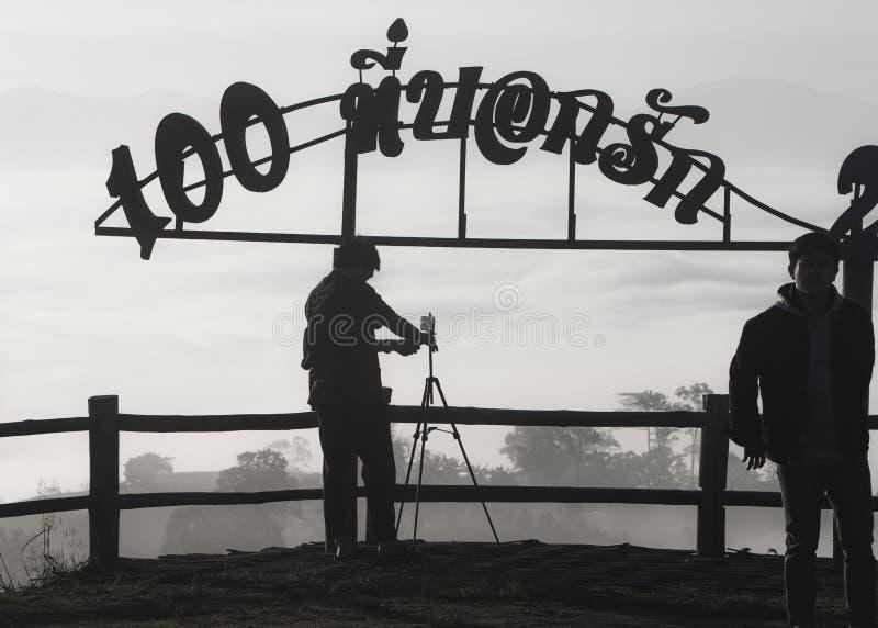 Σκιαγραφία του ατόμου που παίρνει μια εικόνα με το τηλέφωνό του σε ένα τρίποδο, Υ στοκ φωτογραφία
