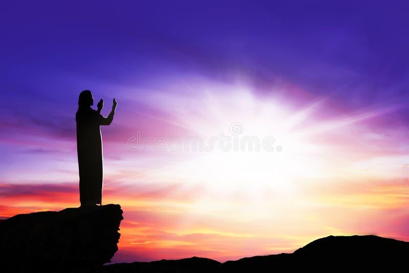 Σκιαγραφία του ατόμου που προσεύχεται στο Θεό με την ακτίνα του φωτός στοκ φωτογραφίες