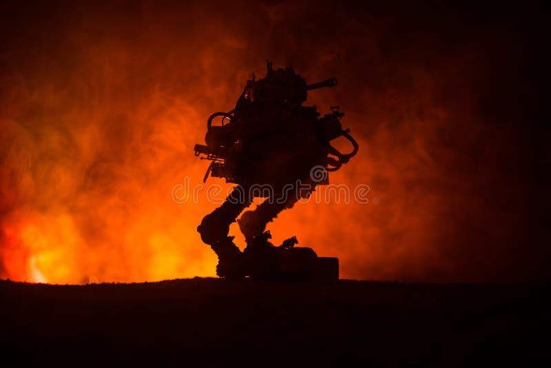 Σκιαγραφία του γιγαντιαίου ρομπότ Φουτουριστική δεξαμενή στη δράση με το ομιχλώδες υπόβαθρο ουρανού πυρκαγιάς στοκ εικόνες