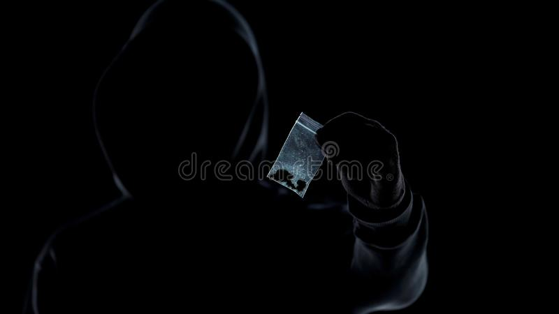 Σκιαγραφία του διακινητή ναρκωτικών που παρουσιάζει πακέτο με τη μαριχουάνα στη κάμερα, εθισμός στοκ εικόνες με δικαίωμα ελεύθερης χρήσης