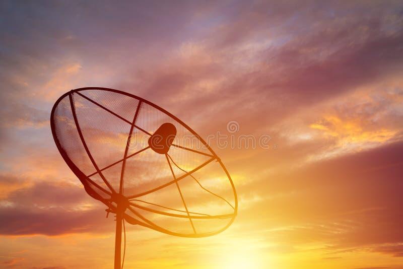 Σκιαγραφία του δορυφορικού πιάτου στο υπόβαθρο ηλιοβασιλέματος στοκ εικόνες