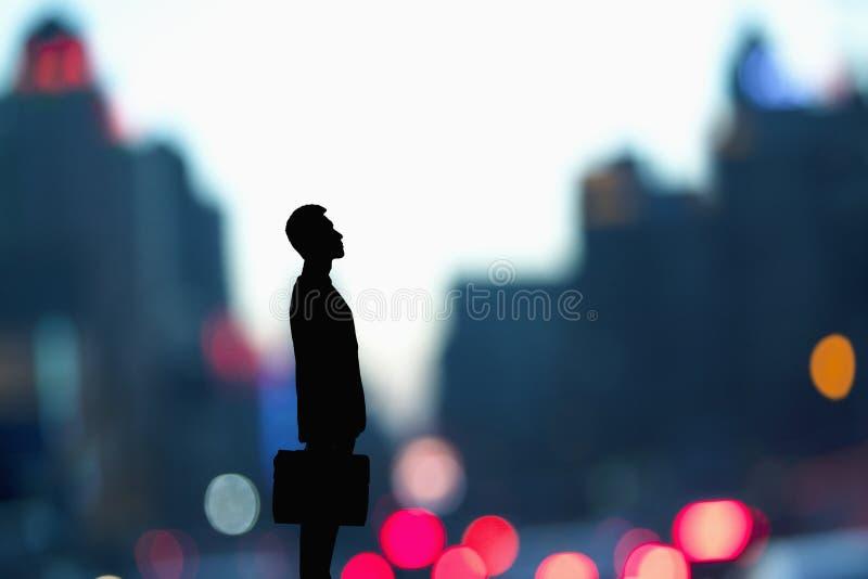 Σκιαγραφία του επιχειρηματία που κρατά έναν χαρτοφύλακα με τα θολωμένα φω'τα πόλεων πίσω από τον στοκ εικόνες
