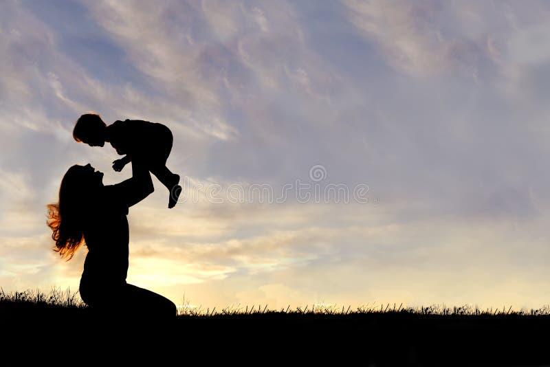 Σκιαγραφία του ευτυχούς παιχνιδιού μητέρων έξω με το μωρό στοκ φωτογραφίες