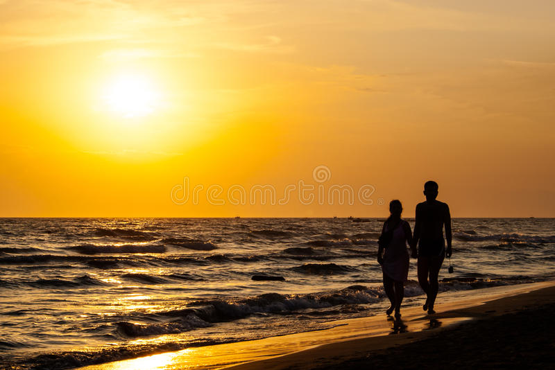 Σκιαγραφία του ζεύγους που περπατά στην παραλία στοκ φωτογραφία