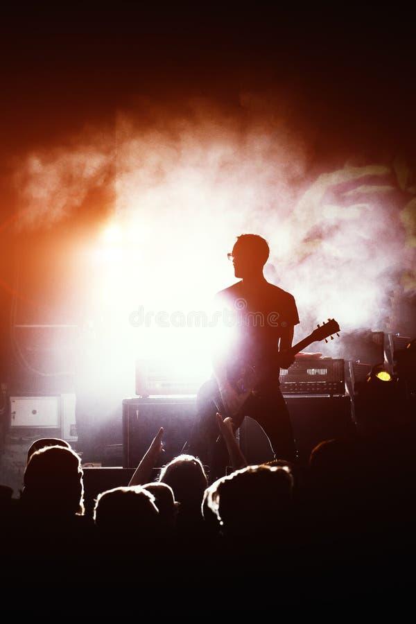 Σκιαγραφία του κιθαρίστα στη δράση στη σκηνή στοκ φωτογραφία
