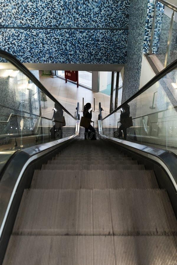 Σκιαγραφία του κοριτσιού που αναρριχείται στις κυλιόμενες σκάλες αερολιμένων με τη βαλίτσα στοκ εικόνες με δικαίωμα ελεύθερης χρήσης