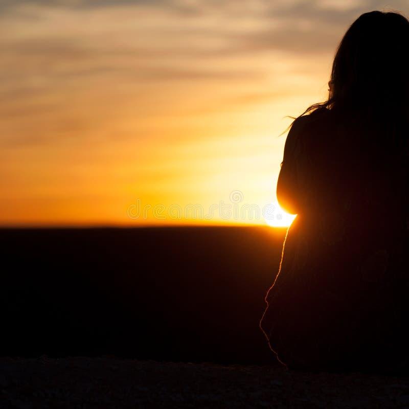 Σκιαγραφία του κοριτσιού που εξετάζει την πορτοκαλιά και κίτρινα ανατολή/το ηλιοβασίλεμα στοκ φωτογραφία με δικαίωμα ελεύθερης χρήσης
