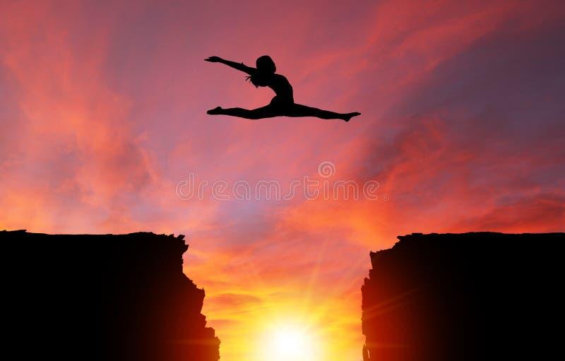 Σκιαγραφία του κοριτσιού που πηδά πέρα από τους απότομους βράχους με το τοπίο ηλιοβασιλέματος απεικόνιση αποθεμάτων