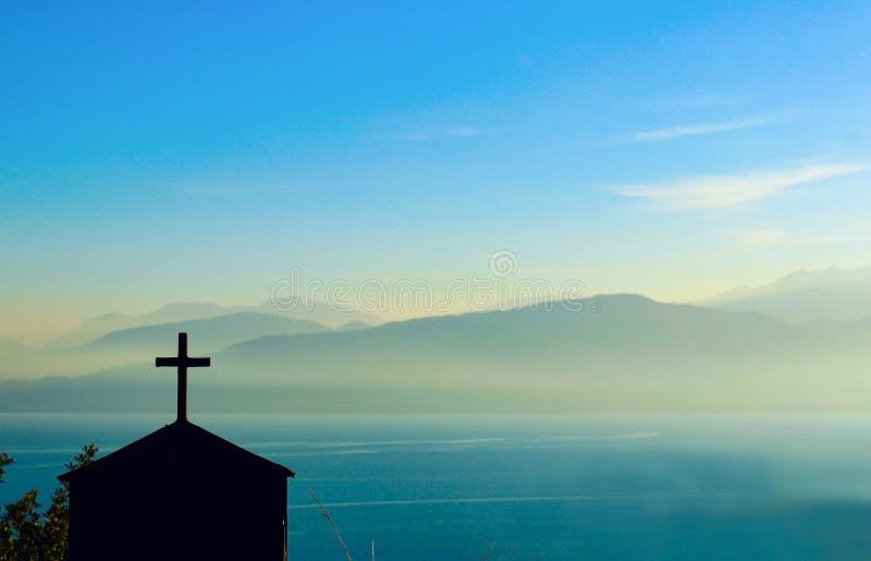 Σκιαγραφία του κτηρίου με το σταυρό στην κορυφή μπροστά από τη σειρά βουνών που θολώνεται από τη βαθιά ομίχλη πέρα από το κανάλι στοκ φωτογραφία με δικαίωμα ελεύθερης χρήσης