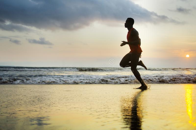 Σκιαγραφία του νέου ελκυστικού κατάλληλου αθλητικού και ισχυρού μαύρου αμερικανικού ατόμου afro που τρέχει στην παραλία ηλιοβασιλ στοκ εικόνα με δικαίωμα ελεύθερης χρήσης