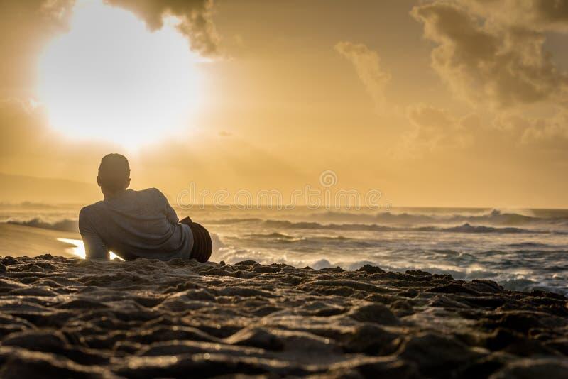 Σκιαγραφία του νέου καυκάσιου αρσενικού που βάζει στην παραλία ηλιοβασιλέματος που εξετάζει έξω το ηλιοβασίλεμα πέρα από τον ωκεα στοκ φωτογραφία με δικαίωμα ελεύθερης χρήσης