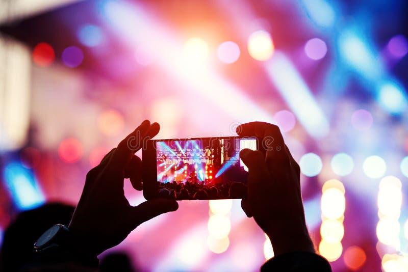 Σκιαγραφία του νεαρού άνδρα, που παίρνει τη συναυλία βράχου φωτογραφιών στο κινητό τηλέφωνο στοκ εικόνα με δικαίωμα ελεύθερης χρήσης