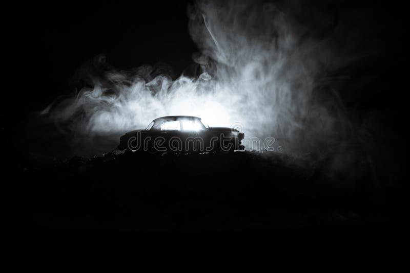 Σκιαγραφία του παλαιού εκλεκτής ποιότητας αυτοκινήτου στο σκοτεινό ομιχλώδες τονισμένο υπόβαθρο με τα φω'τα πυράκτωσης στο χαμηλό στοκ φωτογραφία με δικαίωμα ελεύθερης χρήσης