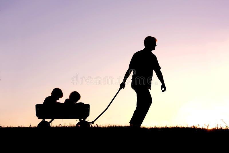 Σκιαγραφία του πατέρα που τραβά τους γιους στο βαγόνι εμπορευμάτων στο ηλιοβασίλεμα στοκ εικόνα με δικαίωμα ελεύθερης χρήσης