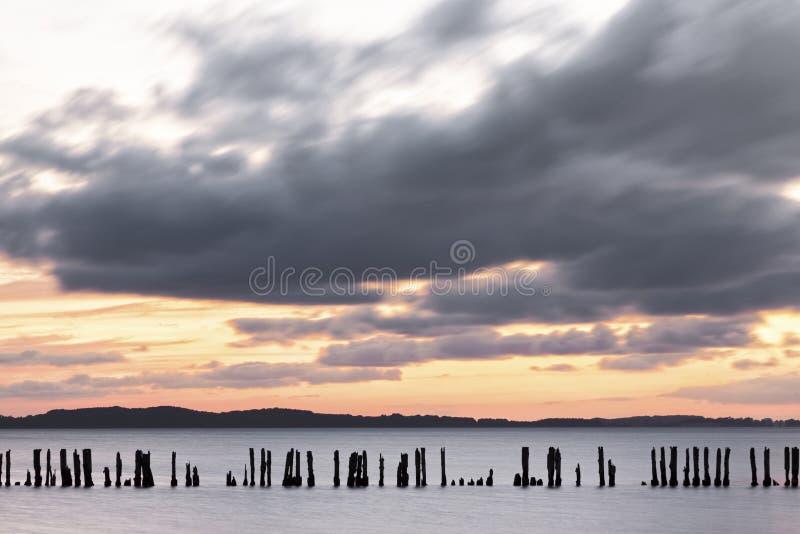 Σκιαγραφία του παλαιού groyne στο σούρουπο στοκ εικόνες