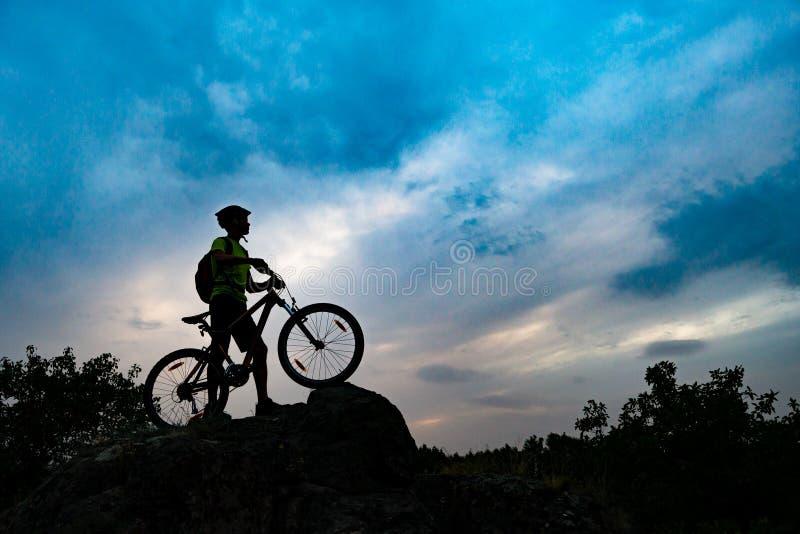 Σκιαγραφία του ποδηλάτη με το ποδήλατο βουνών στο βράχο στο ηλιοβασίλεμα Ακραίος αθλητισμός και έννοια ανακύκλωσης Enduro στοκ φωτογραφία με δικαίωμα ελεύθερης χρήσης
