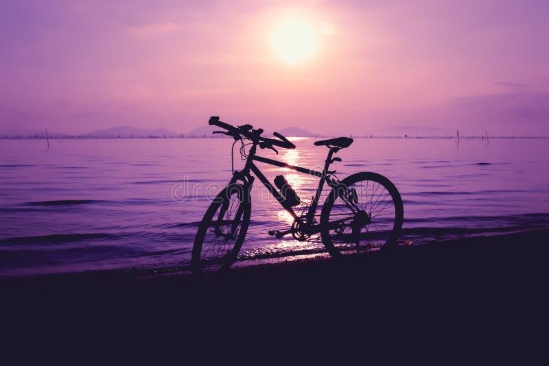 Σκιαγραφία του ποδηλάτου στην παραλία ενάντια στο ζωηρόχρωμο ηλιοβασίλεμα στο θόριο στοκ φωτογραφίες με δικαίωμα ελεύθερης χρήσης