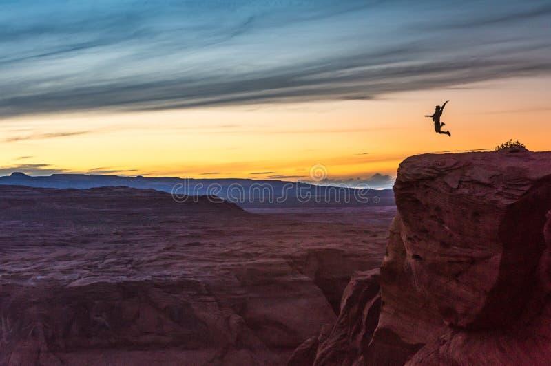 Σκιαγραφία του προσώπου που πηδά επάνω στον απότομο βράχο με το ηλιοβασίλεμα στοκ εικόνα