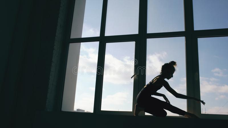 Σκιαγραφία του σύγχρονου χορού απόδοσης χορευτών νέων κοριτσιών στο windowsiil στο στούντιο χορού στο εσωτερικό στοκ εικόνα με δικαίωμα ελεύθερης χρήσης