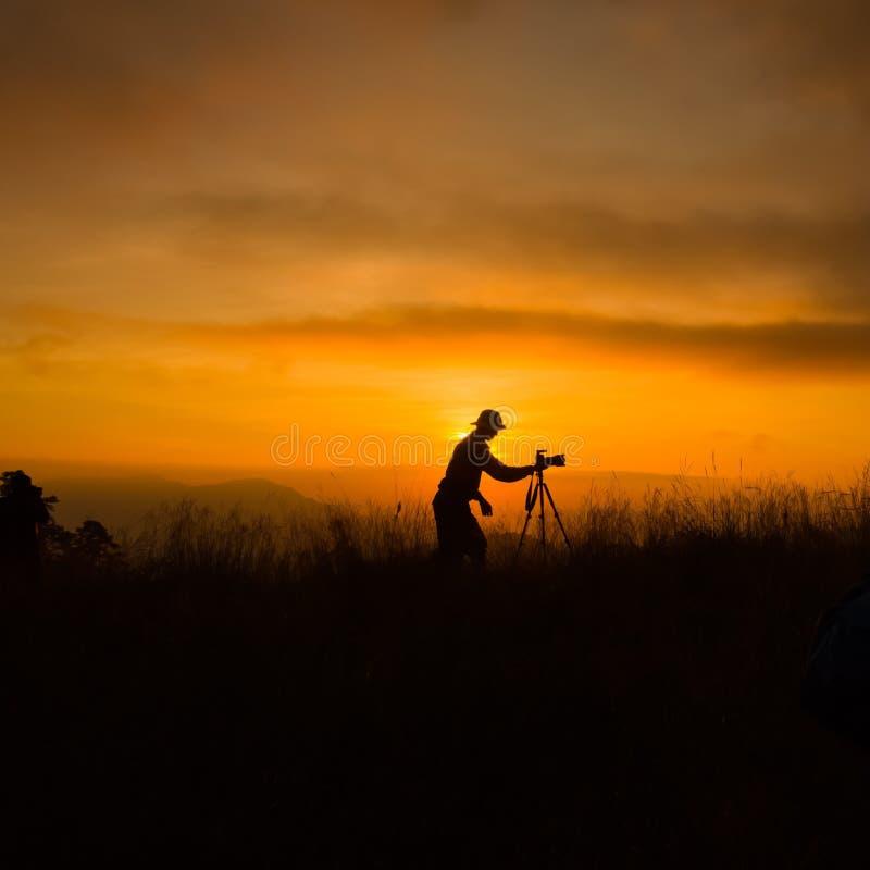 Σκιαγραφία του φωτογράφου που παίρνει την εικόνα στοκ φωτογραφία