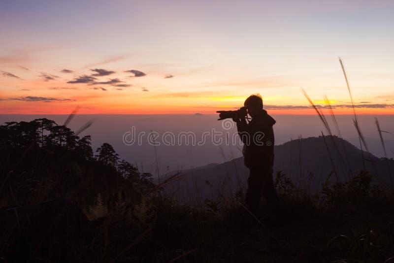 Σκιαγραφία του φωτογράφου που παίρνει την εικόνα στοκ εικόνες