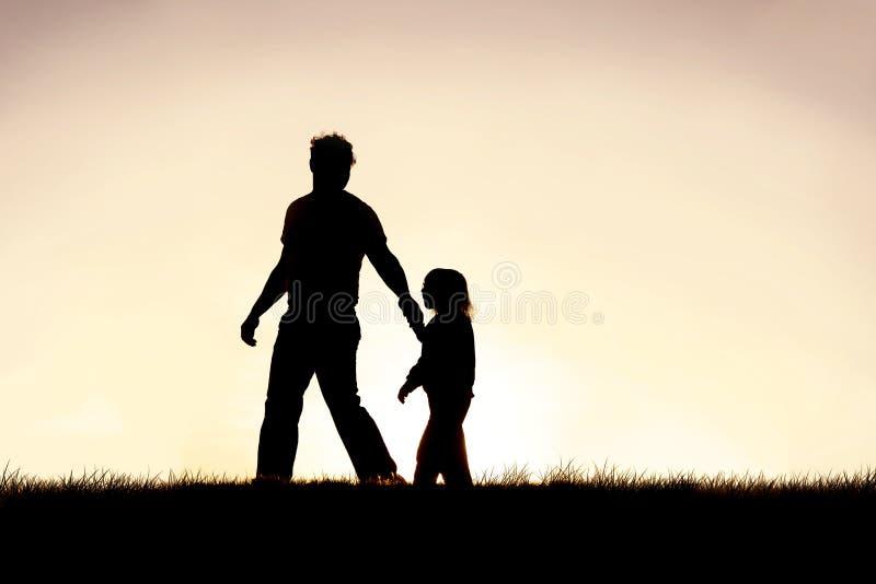 Σκιαγραφία του χριστιανικού πατέρα που καθοδηγεί το μικρό παιδί του από το χέρι στοκ εικόνες
