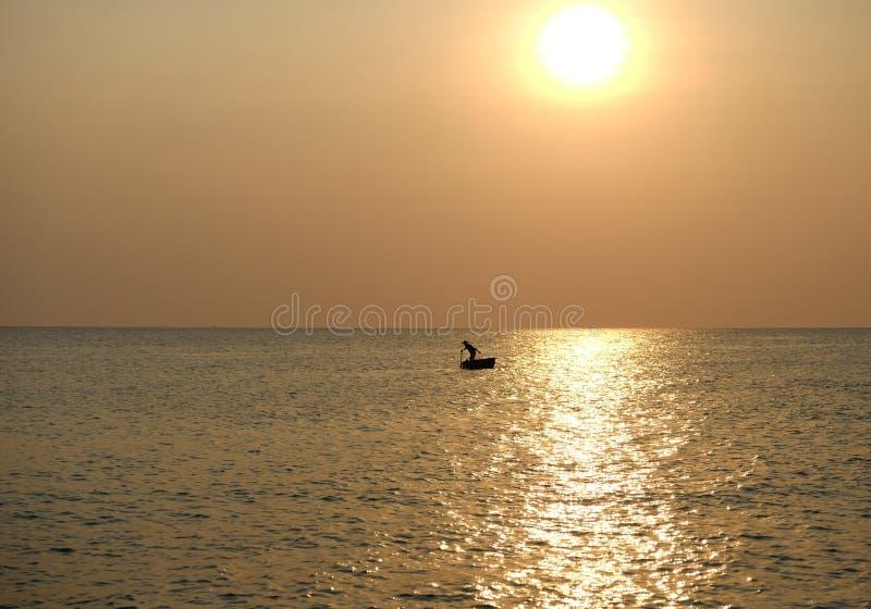 Σκιαγραφία του ψαρά στη θάλασσα στο χρυσό ηλιοβασίλεμα δίπλα στο φωτεινό ήλιος-ξέφωτο στο νερό Phu Quoc, Βιετνάμ στοκ εικόνες