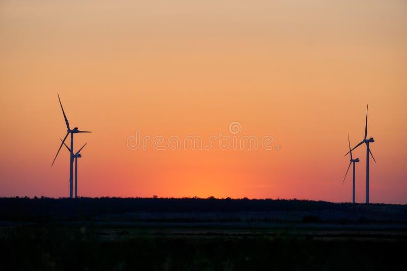 Σκιαγραφία των ανεμοστροβίλων στο ηλιοβασίλεμα Η έννοια του alternativ στοκ εικόνα