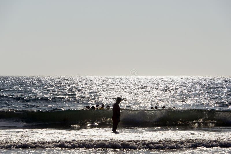 Σκιαγραφία των ανθρώπων που παίζουν, που κολυμπά στα κύματα στο νησί Patmos, Ελλάδα στο θερινό χρόνο στοκ εικόνες