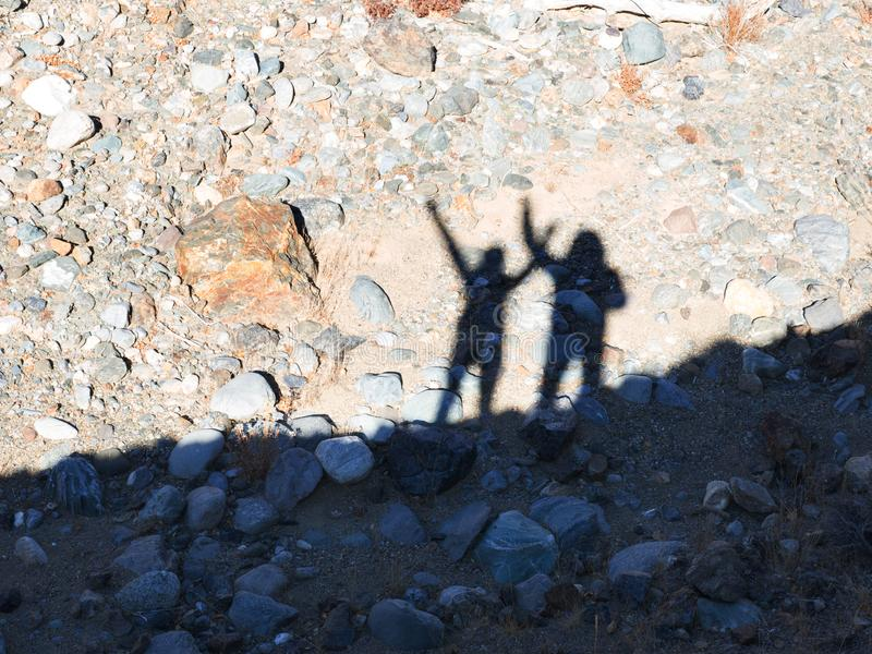 Σκιαγραφία των ανθρώπων που χαιρετούν σας πέρα από το φυσικό υπόβαθρο στο βουνό στοκ εικόνες