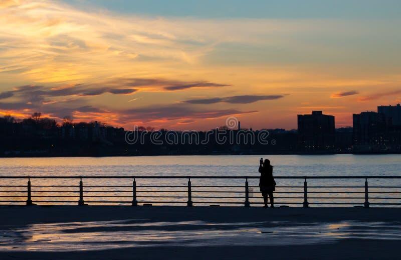 Σκιαγραφία των γυναικών που φωτογραφίζουν το ηλιοβασίλεμα στην πόλη της Νέας Υόρκης στοκ εικόνες